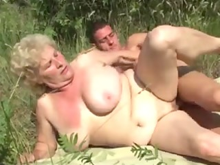 german granny outdoor with young fellow by troc